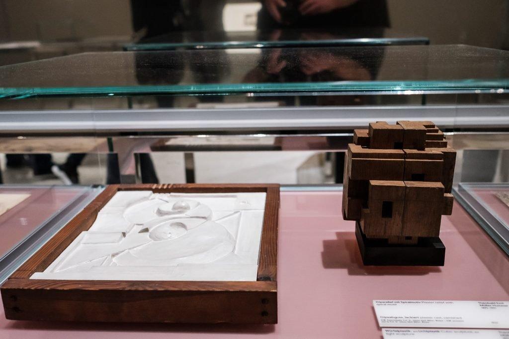 Ein Gipsabdruck links und eine Würfelplastik aus Eichenholz rechts